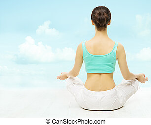 Yoga woman back view meditate sitting in lotus pose over sky