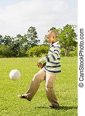 african boy kicking soccerball - african teen kicking...