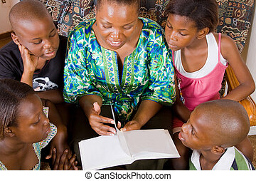 enjoying a story - mom reading to her kids who are enjoying...