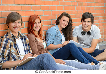 Group of friends students sitting in row against brick wall
