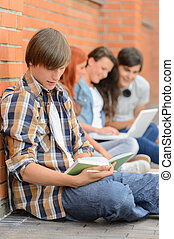 Young man studying book friends in background