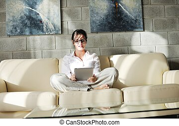 woman using tablet pc at home - Young woman at home relaxing...