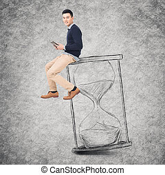 time management - Asian young man sit on a hourglass and use...