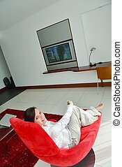 young woman watching tv at home - happy young woman watching...