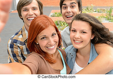 Group of student teenage friends taking selfie laughing at...