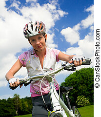 Girl with bicycle. Close shot - Cyclist girl looking at...