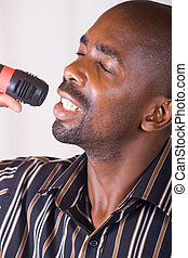 african singer - african man singing with microphone in air