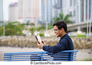 Portrait of asian office worker with ipad on bench -...