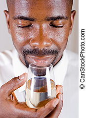wine tasting - african man sniffing and tasting a glass of...