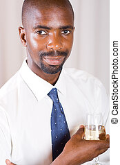 african man with wine - african man in suit enjoying a glass...