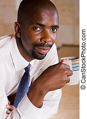 man drinking coffee - african man drinking coffee on a break