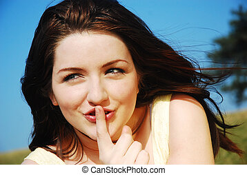 Shh - Beautiful young woman saying shh with her finger to...