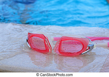 Swimming goggles beside the pool.
