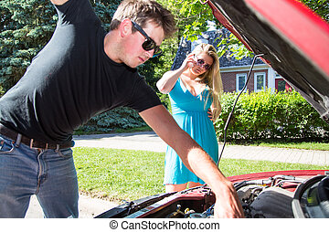Calling for roadside assistance - A young man checks under...