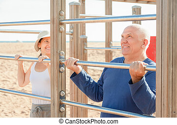 Sporty mature couple training with chin-up bar in summer