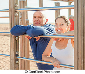 senior couple training on pull-up bar - Mature couple...