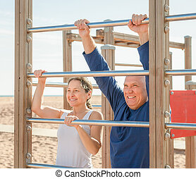 mature couple training with chin-up bar in summer - senior...