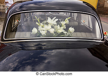 flowers decorating an old black luxury car