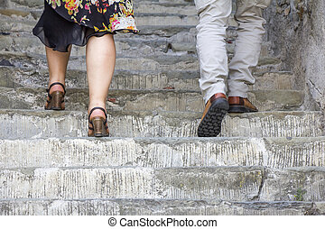 Climbing on stone stairs - A woman and man climbing on stone...