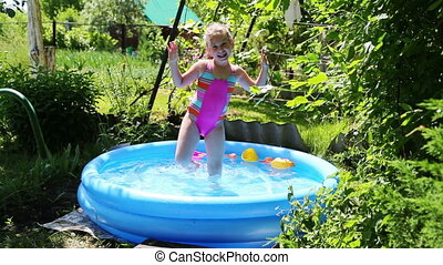 cheerful girl in inflatable pool in summer garden