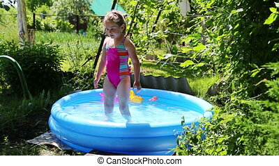 cheerful girl in inflatable pool in summer garden -...