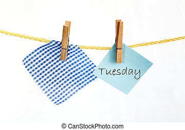 Note colored paper with the word Tuesday - The paper notes...