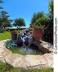 Small fountain water feature including greek urn, enclosed...