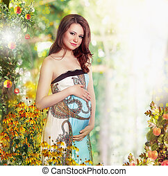Maternity. Pregnant Smiling Woman in Nature Expecting Baby