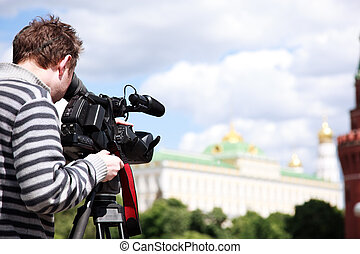 Cameraman filming - man with HD camcorder on tripod,...
