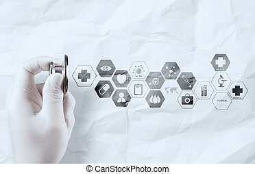 hand holding stethoscope shows medical icons on crumpled paper a