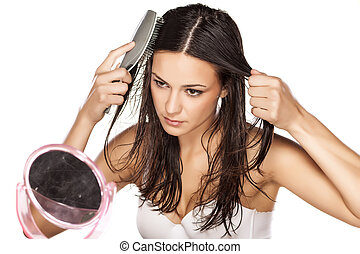 wet hair combing - beautiful young woman comb her wet hair