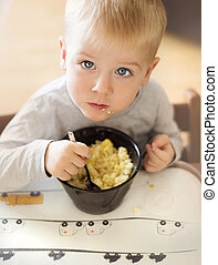 Little boy eating - Cute little blonde boy eating pasta from...