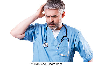 Depressed surgeon. Side view of depressed mature doctor touching his face with hand and keeping eyes closed while standing isolated on white