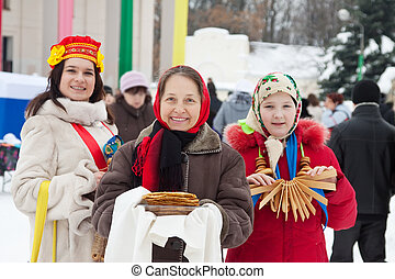 women in russian traditional clothes during Shrovetide -...