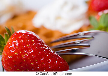 waffles and strawberries - a plate with waffles and...