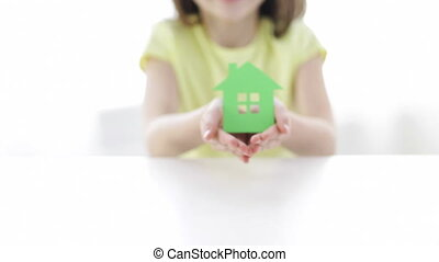 close-up of smiling girl holding paper house - home,...