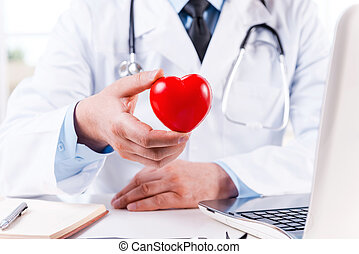 Taking good care of your heart. Close-up of doctor holding heart shape toy while sitting at his working place