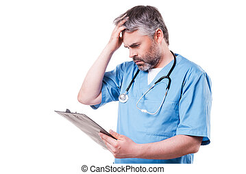 Bad news. Frustrated mature surgeon in blue uniform holding hand in hair and looking at his clipboard while standing isolated on white