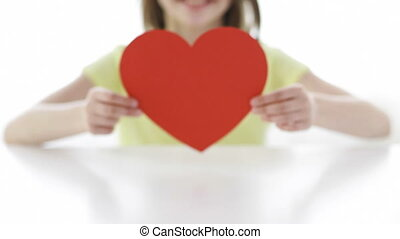 close-up of smiling girl with red heart at home - love,...
