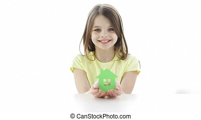 smiling girl holding paper house - home, happiness and...