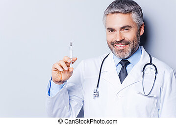 Time for injection Confident mature doctor holding syringe...