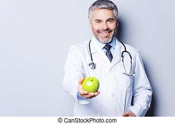 Eat healthy! Cheerful mature doctor in giving a green apple...