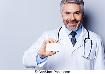 Doctor holding business card. Cheerful mature doctor showing his business card and smiling while standing against grey background