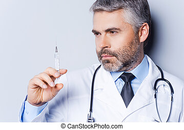 Doctor with syringe Confident mature doctor holding syringe...