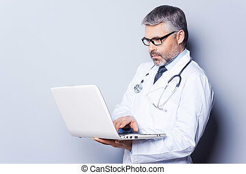 Doctor with laptop Confident mature doctor working on laptop...