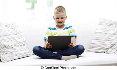 smiling boy with tablet pc computer at home - home,...