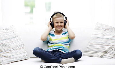 smiling little boy in headphones at home - childhood,...