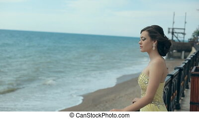 Tender young girl in gorgeous lemony strapless dress stay...