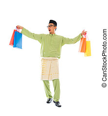Traditional Malay male shopping and jumping in joy during...