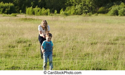 Mother and her son playing bo-peep outdoor - Panning shot of...